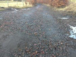The road is covered with largish cobbles/ stones imbedded and loose in the road making the road very uneven.