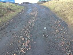 Near the top, next to the farm. Loose and hard pack gravel. Uneven.