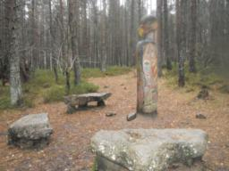 Natural stone from around the site has been used to create a rest area. These are situated around a  Totem Pole.