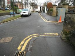 There is a driveway entrance that breaks the pavement. The kerbs are not flush with road.