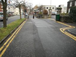 The pavement joins the road on approach to the crossing. The pavement is not flush with the road.