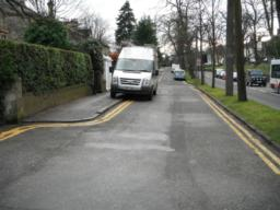 The pavement joins the road.  The pavement is not flush with the road.