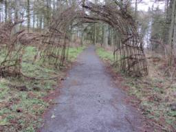 Proceed uphill past a willow arch.