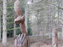 Wooden sculptures are placed alongside the trail.