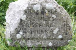 A milestone gives distances to Barnstaple and Bideford.