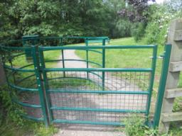 The width of the kissing gate is 1.2m (and when opened has an internal clearance of 1m). The  gate opens in only one direction, into the metal hooped enclosure, and the latch mechanism is located on the inside of the gate.