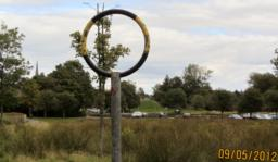 The train use to travel past the red cross and put the post in a net in this black and yellow hoop