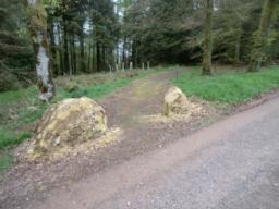 Approximately 100 yards from exit to Car park there is a 'gateway' on the left marked by two large boulders 1.6 metres apart. Pass through the gateway onto hard-packed gravel path and continue forwards.