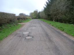 View along 4-metre wide gravel road leading back to the car park approximately 200 metres away. The first 100 metres  section is relatively flat but does have occasional potholes.