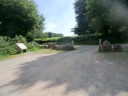 The starting point for the walk (the information board in the Chargot Woods car park) can be seen on the left hand side of the photo. To begin the walk exit the car park through the 3-metre wide gateway (seen on  right of photo) at the eastern end of the car park and turn left onto a 3 metre wide hard-packed gravel road.