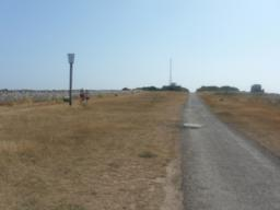 The tarmac track  ends about 50 metres before the lighthouse. This last section is a wide rough stony track, with smoother grass on either side.