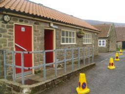 A toilet block including an accessible toilet is adjacent to the car park.