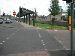 Controlled pedestrian crossing across road entrance to bus station. Dropped kerbs and tactile paving in place.
