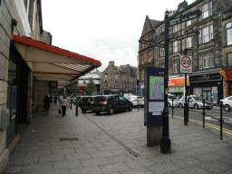 Start of the city centre. There is an information board, sign post, shelter under shop canopy, ATM and litter bins. The pavement remains wide.