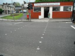 Controlled pedestrian crossing with dropped kerbs.