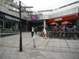 City centre amenities incluing sign posts, cafes and one of entrances to the Thistle Shopping Centre where there are shops, cafes, toilets and seats.