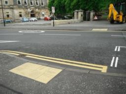 Dropped kerbs and tactile paving at crossing point.