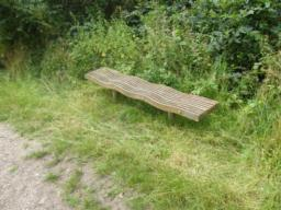 Wavy bench in rough grass off path; bench is low to the ground.