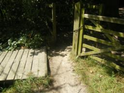 Very tight gap between gate and short wooden bridge, distance of 0.5 metres.