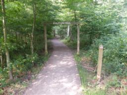 Sculpture Trail begins under a wooden arch. Note the way-marking post with  circular green 'Easy Access Route' described. This is the anti-clockwise route, which keeps uphill gradients to a minimum.