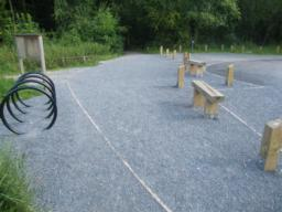 Two benches at the west car park constitute the seventh of eight seats. Surface is gravel.