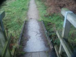 There is a small step where the bridge ramp meets the path.