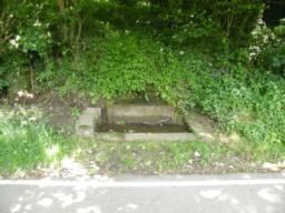 Historic stone horse trough, filled by natural spring running towards reservoir.