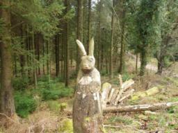 A right turn and a short distance lead to a junction where there is a carving of a hare.