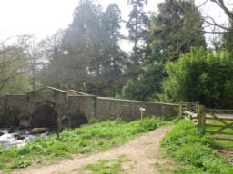 There is another gate (1m) before the trail crosses a bridge over the river Avill to follow a level path along the edge of a farm field.