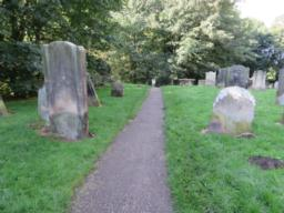 Narrow firm surfaced path continues on the level through the graveyard behind the church.