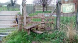 There is a stile to the right of the entrance gate