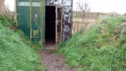Doorway is 72cm wide.  There is a wire mesh door that opens outwards towards the right.  There is 1m long section of boardwalk at the entrance of the hide.