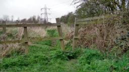 Squeeze through stile 54cm wide at the top, 19cm wide at the bottom with a step 19cm high.  After stile, do not bear right as there is a ditch. Go forward 18m then turn left through wide gateless opening.