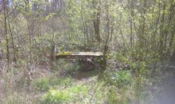 Tom's bench is on the left.  The bench has no back.  The path back to the lay-by is just to the right of the bench.   Follow the path and boardwalk to return to the road.