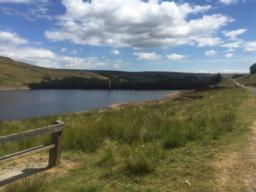 A bench on the well surfaced track with views over Scar House Reservoir towards the dam wall.