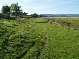 The path leads towards the shore near the railway bridge across the estuary.