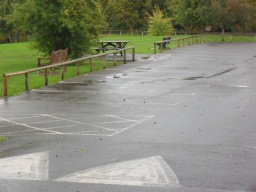 Large car park with one generous accessible parking bay in the middle of the car park.  There is a picnic bench adjacent to the bay
