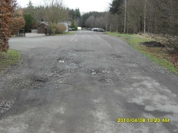 A short section of the road has pot holes across its width.