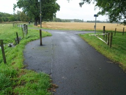 There is a barrier across the road which is open most of the time. There is a gap to the side 800mm wide.