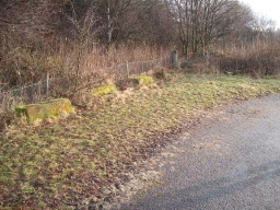 There are some stone blocks to the side of the road that could provide a seat to rest on.
