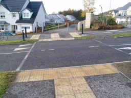 There is a well marked crossing on Alloa Park Road.Go straight on through the gap beside the vehicle barrier.