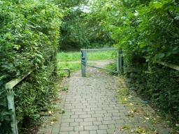 From the seating area there is a short paved path to a self closing gate without a latch which leads onto the trail.