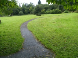 The path is narrow but level across the play area field.