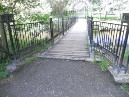 From the path, there is a step level rise leading onto  Castle Bridge measuring 40mm. There are also breaks / gaps in between the wooden decking boards.