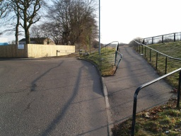 Head towards the barrier where there is a gap to the side onto the continuation of the tow path.