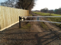 The gap next to the locked barrier is wider than 1m but the sruface of the ground is uneven.