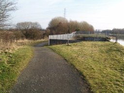 There is a slope away from the tow path with a gradient of 13% (1 in 8) on an uneven surface.