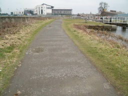 The path has an uneven surface in places.
