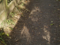 The floor of the bridge has a metal grill covering with some loose edges.