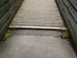 There is a small step or tread obstacle at the bridge.